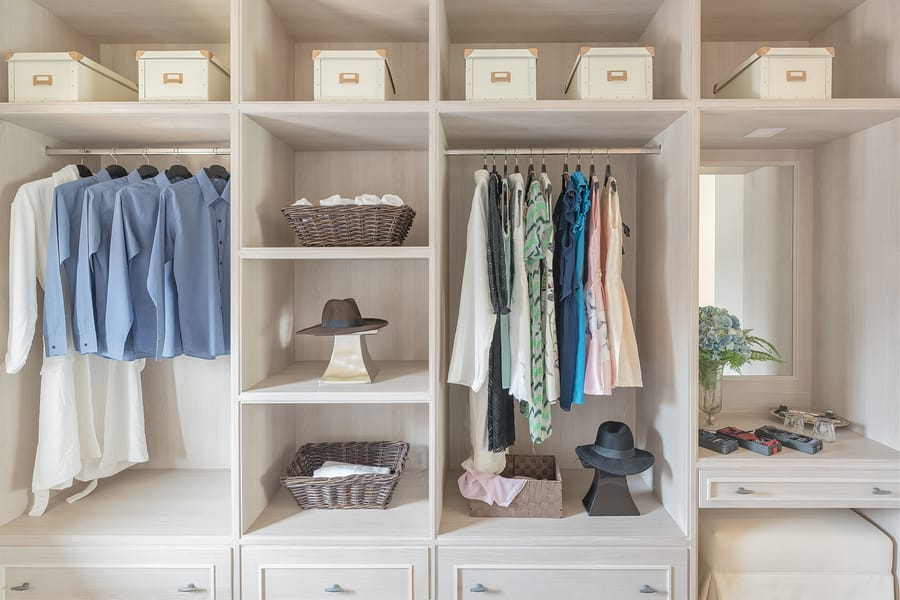 modern walk in closet with clothes hanging on rail