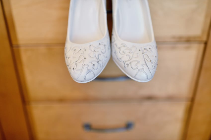 wedding shoes hanging from a dresser